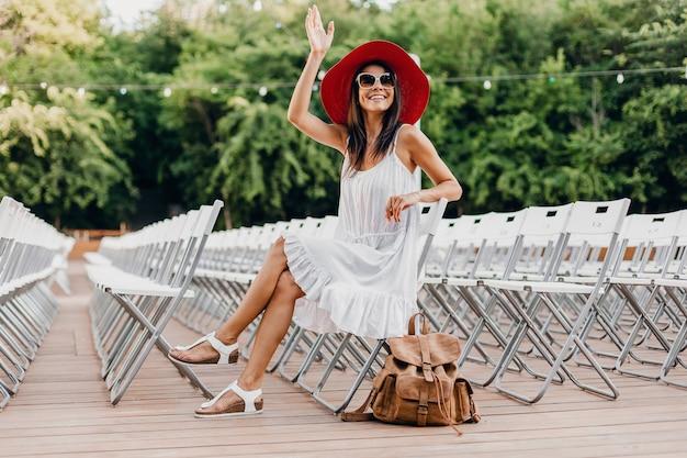 Attraktive frau gekleidet in weißem kleid, rotem hut, sonnenbrille, die im sommer freilufttheater auf stuhl allein sitzt, modetrend des frühlingsstraßenstils, accessoires, reisen mit rucksack, winkende hand