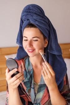 Attraktive frau im bademantel, duschtuch auf dem kopf bereitet sich auf make-up vor, pinsel in der hand