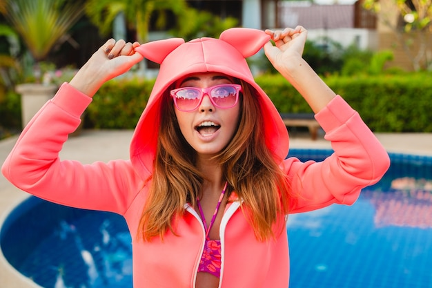 Attraktive frau im bunten rosa kapuzenpulli, der sonnenbrillen auf sommerferien lächelndem emotionalen gesichtsausdruck trägt, der spaß, sportmode-stil hat