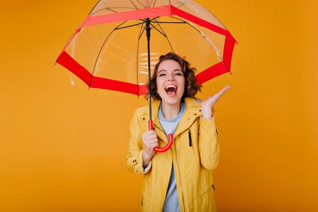 Attraktive frau im gelben herbstmantel, der positive gefühle ausdrückt. raffiniertes mädchen mit kurzen lockigen haaren, die unter regenschirm lachen.