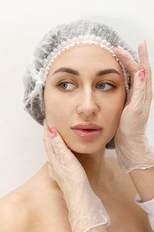Attraktive frau im medizinischen hut bei kosmetikerin