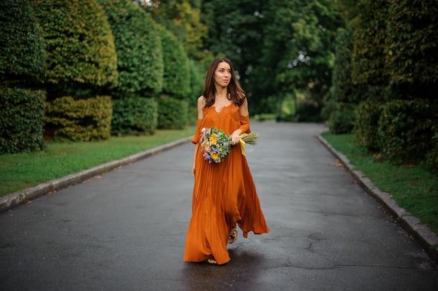 Attraktive frau im orange kleid gehend auf die straße mit blumenstrauß von blumen
