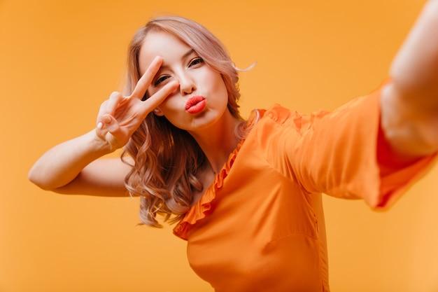 Attraktive frau im orangefarbenen kleid, das selfie macht