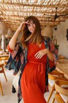 Attraktive frau im orangefarbenen trendigen kleid posinng im tropischen café. helles outfit. reise- und urlaubsmodekonzept.