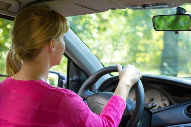 Attraktive frau im rosa die fahrt in ihrem auto genießend