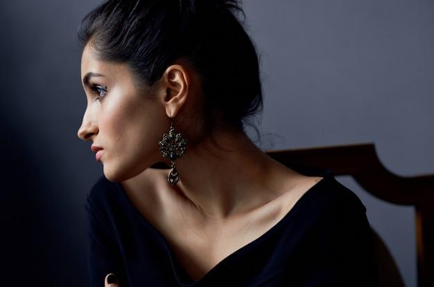 Attraktive frau im schwarzen kleid ohrringe make-up eleganten stil studio