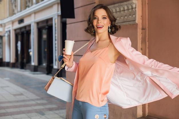 Attraktive frau im stilvollen outfit, das in stadt, straßenmode, frühlingssommertrend, lächelnde fröhliche stimmung geht, rosa jacke und bluse trägt, herumwirbelt, verlassen, fashionista beim einkaufen