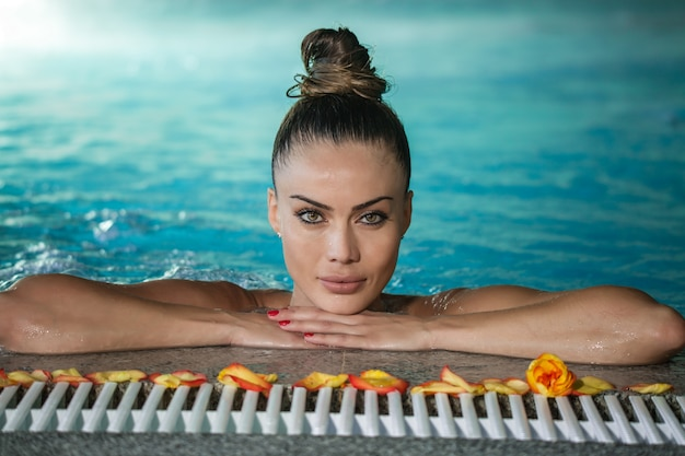 Attraktive frau im swimmingpool mit den blumenblättern