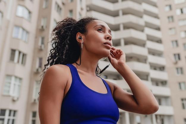Attraktive frau im urbanen sport-fitness-outfit auf dem dach, das training macht, selbstbewusste, lockige frisur, athletischer körper, starke muskeln, die musik über kopfhörer hören