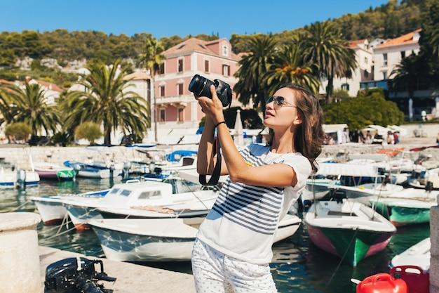 Attraktive frau im urlaub in europa am meer auf einer kreuzfahrt, die fotos vor der kamera macht