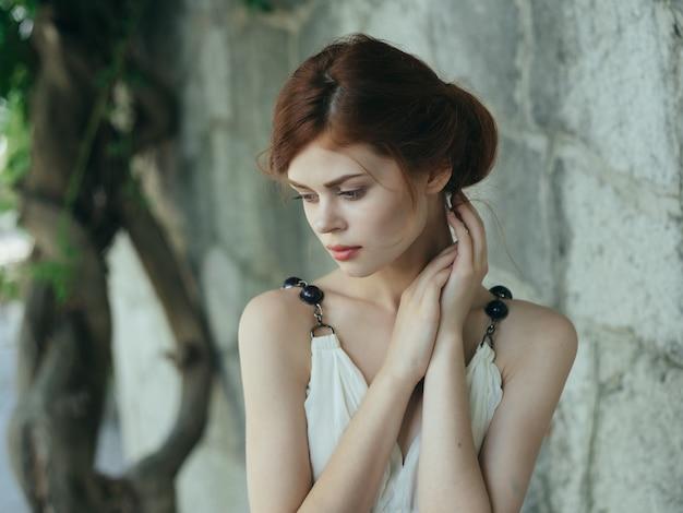 Attraktive frau im weißen kleid nahe der steinmauer des baumes. foto in hoher qualität