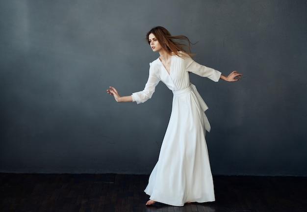 Attraktive frau im weißen kleid tanzleistung charme grau hintergrund modell