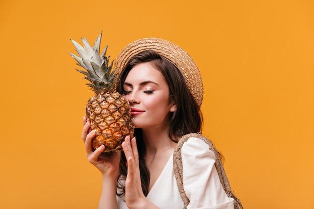 Attraktive frau im weißen t-shirt schnüffelt duftende ananas auf orange hintergrund.