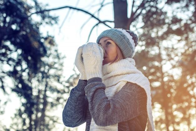 Attraktive frau im winter heißen tee auf sonnenlicht trinkend