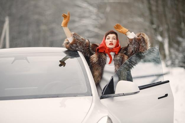 Attraktive frau im winter im freien mit weißem auto