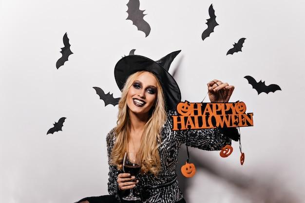 Attraktive frau im zaubererkostüm, das halloween feiert. atemberaubendes blondes mädchen im hexenhut, das maskerade genießt.