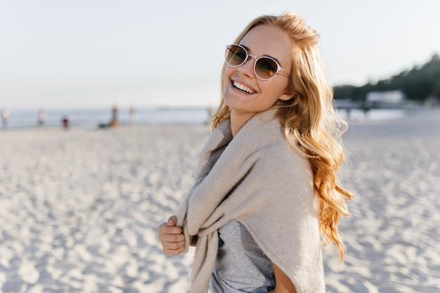 Attraktive frau in brauner sonnenbrille lacht am strand