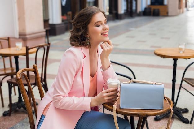 Attraktive frau in der romantischen stimmung, die im glück lächelnd am tisch sitzt, rosa jacke tragend, stilvolle kleidung, auf freund auf einem datum im café wartend, cappuccino trinkend, verlassenen gesichtsausdruck