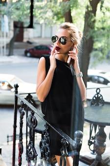 Attraktive frau in der sonnenbrille im schwarzen kurzen kleid, das zigarette auf terrasse raucht. sie telefoniert und schaut zur seite.