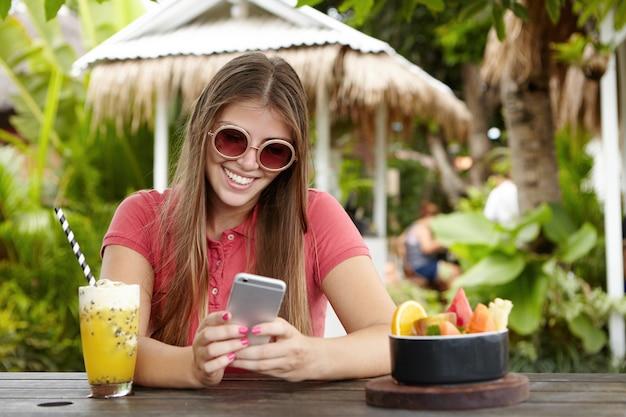 Attraktive frau in der stilvollen sonnenbrille, die smartphone hält und mit glücklichem blick lächelt, während sie nachricht von ihrem freund während des urlaubs im tropischen land liest.