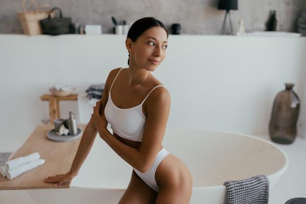 Attraktive frau in der wäsche, die nahe dem bad aufwirft. mädchen posiert für die kamera