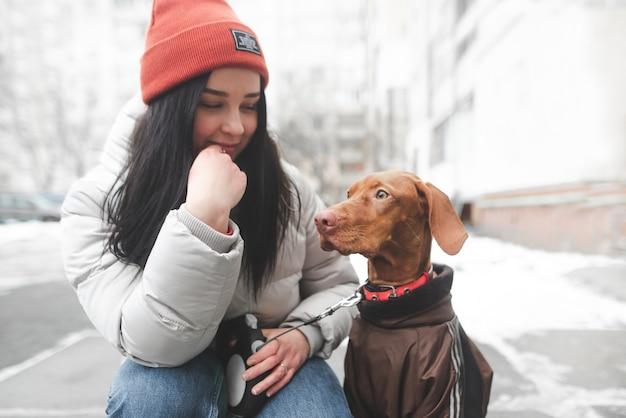 Attraktive frau in der warmen kleidung, die auf der straße mit einem hund sitzt