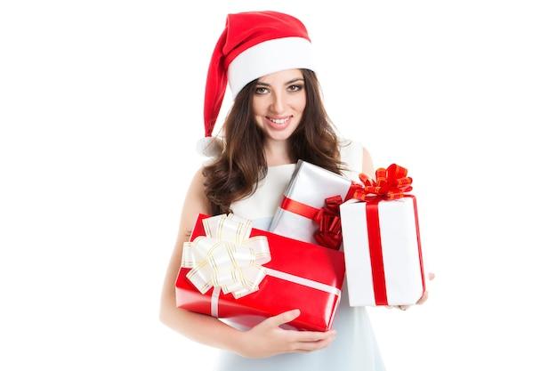 Attraktive frau in der weihnachtsmütze, die geschenke lokalisiert hält. konzept des verkaufs und des weihnachtseinkaufs.