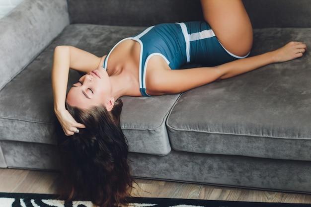 Attraktive frau in dessous, die auf einer couch sitzen