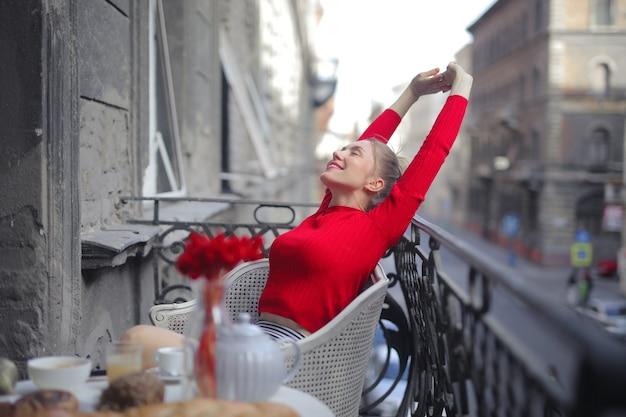 Attraktive frau in einem roten hemd, das auf einem balkon mit einer schönen ansicht sitzt