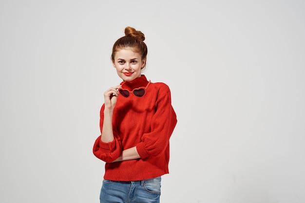 Attraktive frau in einem roten pullover und jeans