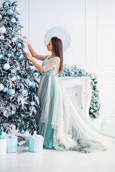 Attraktive frau in einem sanften abendkleid schmückt den weihnachtsbaum in einem gemütlichen haus.