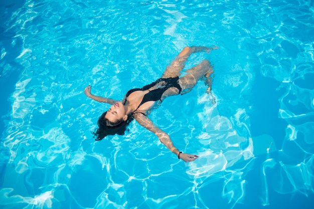 Attraktive frau in einem schwarzen badeanzug, der zurück auf sie in den swimmingpool schwimmt und sich entspannt