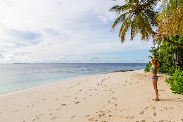 Attraktive frau in einem süßen badeanzug, der am strand am meer steht