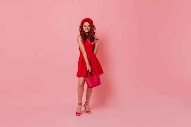 Attraktive frau in fersen nimmt brille ab und schaut in die kamera. lockiges mädchen gekleidet im roten kleid, das mit handtasche im rosa studio aufwirft.