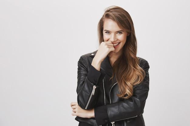 Attraktive frau in lederjacke, lachend und lächelnd