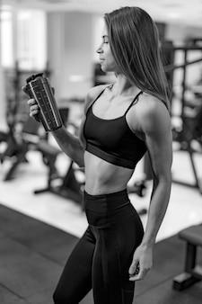 Attraktive frau in sportkleidung. sportlerin mit sportlicher wasserflasche in der hand. sportliches hübsches junges mädchen, das auf unscharfem sportgymnastikhintergrund steht.