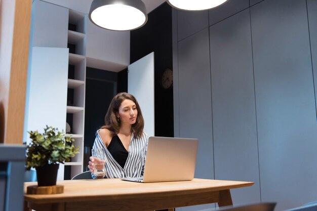 Attraktive frau in stilvollem outfit, die ein glas klares wasser hält und auf den computerbildschirm schaut computer