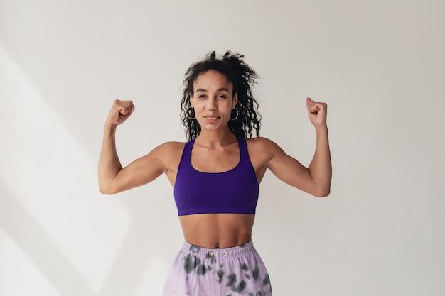 Attraktive frau in stylischem hipster-fitness-outfit mit violettem oberteil und hose auf weißer, isolierter wand
