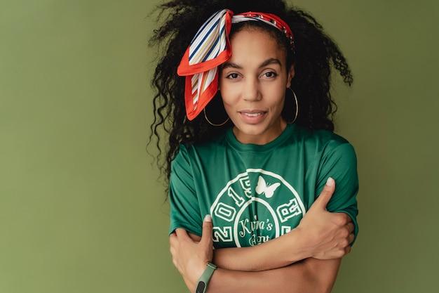 Attraktive frau in stylischem hipster-outfit-t-shirt und shorts an grüner studiowand