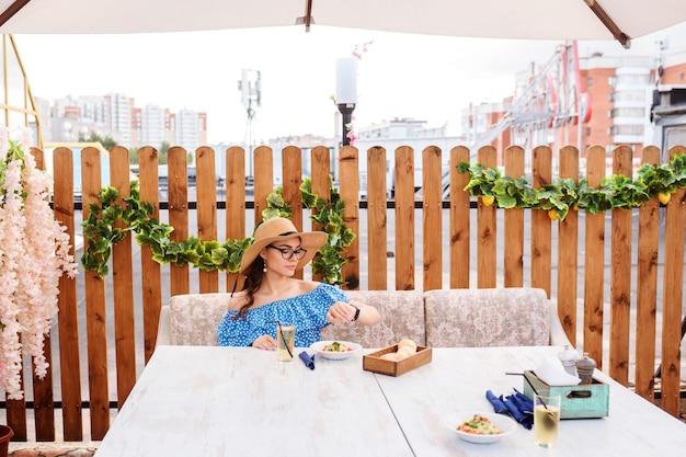 Attraktive frau isst zu mittag, speist in der veranda des cafés im freien und schaut auf ihre uhren.