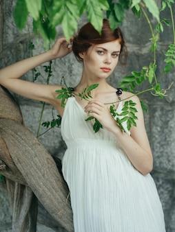Attraktive frau kleidet grünes blattdekorationsmodell. hochwertiges foto