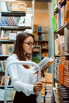 Attraktive frau liest ein buch, während sie in der bibliothek steht