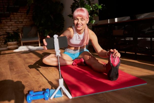 Attraktive frau macht kopf-zu-knie-übungsvideo für fitness-blog im sonnigen raum