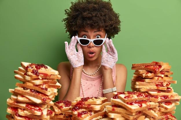 Attraktive frau mit afro-haaren, umgeben von erdnussbutter-gelee-sandwiches