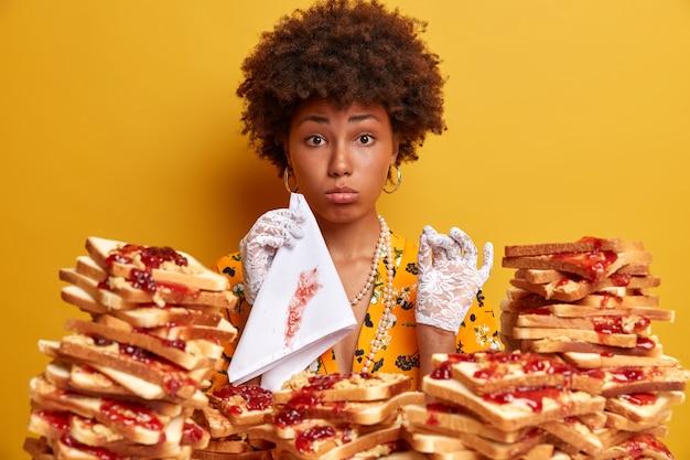 Attraktive frau mit afro-haaren, umgeben von erdnussbutter-gelee-sandwiches Kostenlose Fotos