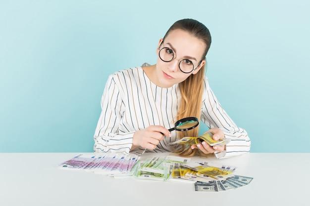 Attraktive frau mit bargeld und lupe