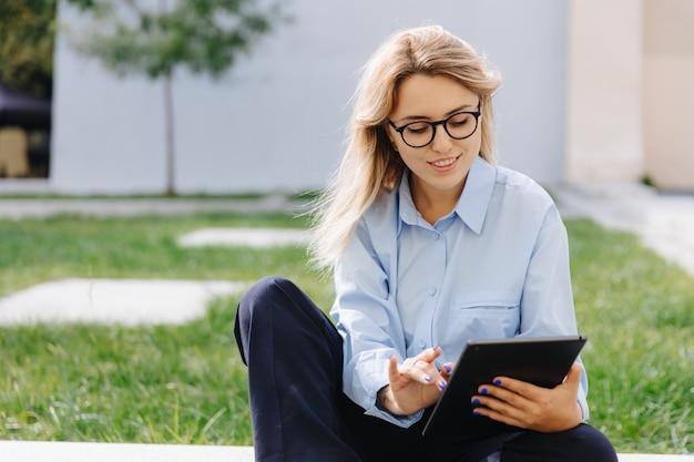Attraktive frau mit blonden haaren, die an der grenze im städtischen raum sitzt und digitale tablette verwendet. glückliche dame in den brillen, die draußen im internet surfen.
