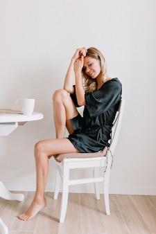 Attraktive frau mit blonden haaren im morgenkleid beim frühstück auf der weißen küche am morgen in der stadt. sie hält eine tasse und schloss die augen mit einem lächeln