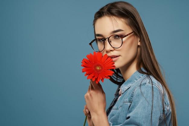 Attraktive frau mit brille rote blumendekoration mode blauen hintergrund