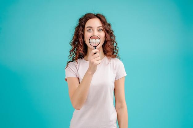 Attraktive frau mit dem lockigen haar, das zähne durch vergrößerungsglas zeigt